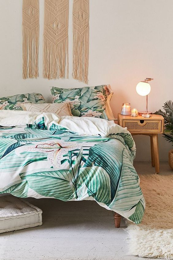 a boho tropical bedroom with rattan and cane furniture, a macrame hanging, bright tropical print bedding and a fluffy rug
