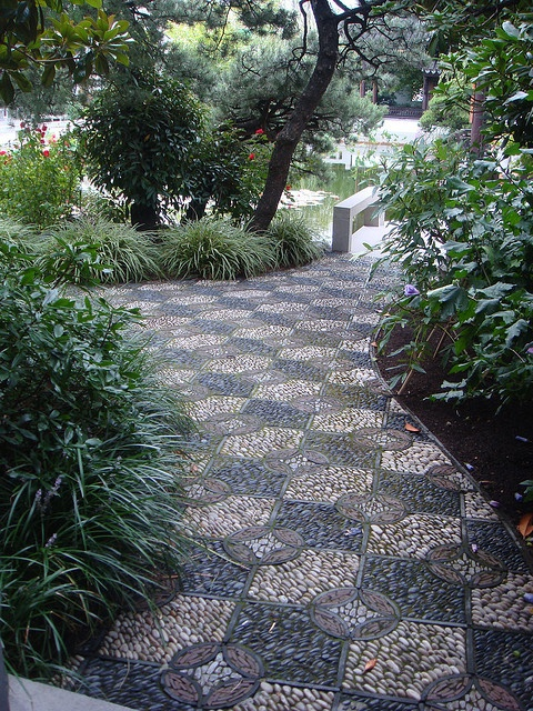 a bold and catchy garden path with black, burgundy, neutral pebbles and geometric patterns