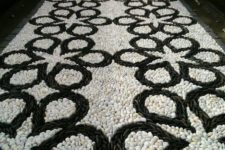 a bold black and white pebble garden path with a catchy pattern is a mosaic decoration
