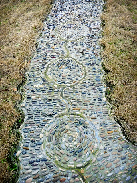 a bold pebble garden path with pebbles of various shades and with a catchy pattern plus curved borders