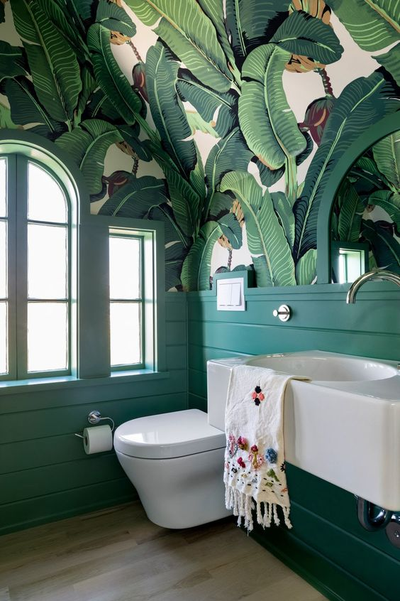 a bold retro bathroom with banana leaf wallpaper on the ceiling, emerald paneling, a floating vanity and arched windows