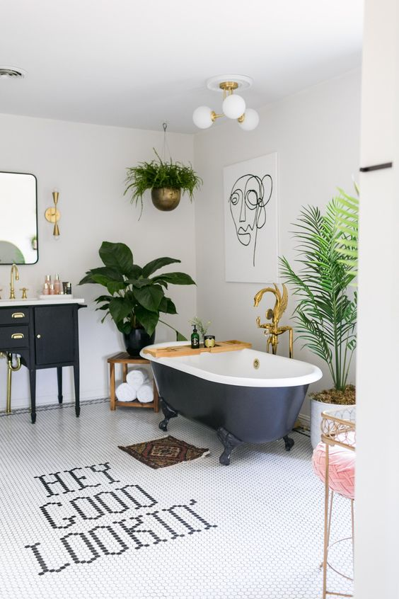 a bold tropical bathroom in neutrals, with a black vanity and a tub, potted greenery, gold touches and a pink stool