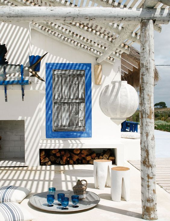 a bold white and blue beach patio with framed shutters, white furniture, striped textiles, a paper lamp and blue accessories
