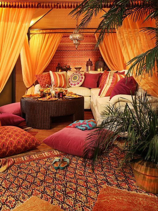 a bright Moroccan lounge with colorful pillows, a low wicker table, a Moroccan lantern with potted greenery
