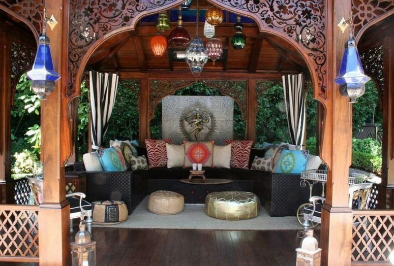 a bright Moroccan patio with a U-shaped sofa, colorful pillows and glass lanterns, leather ottomans and carvings