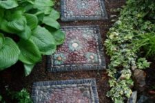 a bright and catchy pebble pathway with tiles covered with burgundy, black and grey pebbles on top