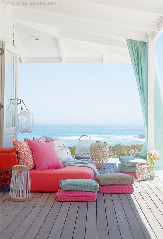 a bright beach deck with colorful furniture, cushions and textiles, candle lanterns and turquoise curtains and a gorgeous sea view