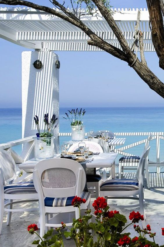 a bright blue and white beach patio with a dining set, bright chairs, some blooms and a tree and a fantastic view
