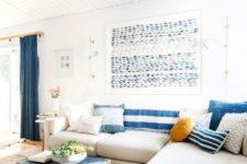 a bright coastal living room with striped pillows, a blue chest, an artwork, blue curtains and a neutral sofa