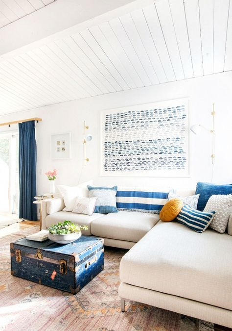 a bright coastal living room with striped pillows, a blue chest, an artwork, blue curtains and a neutral sofa