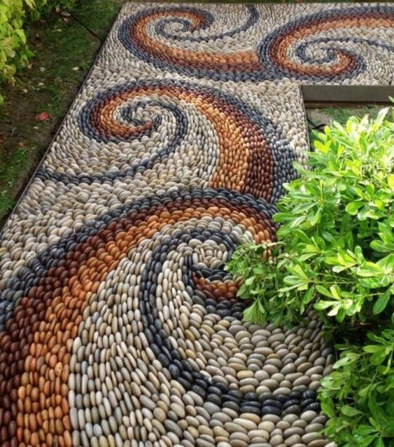 a bright pebble path with blue, white, burgundy and rust pebbles and swirl patterns