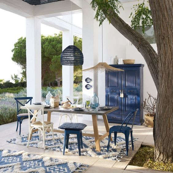 a bright seaside patio in blue and white, with a wooden table and white and navy chairs and stools, pendant lamps and a navy sideboard
