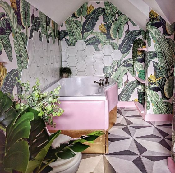 a bright tropical bathroom with banan leaf wallpaper, marble hex tiles, a pink and gold clad bathtub is lovely