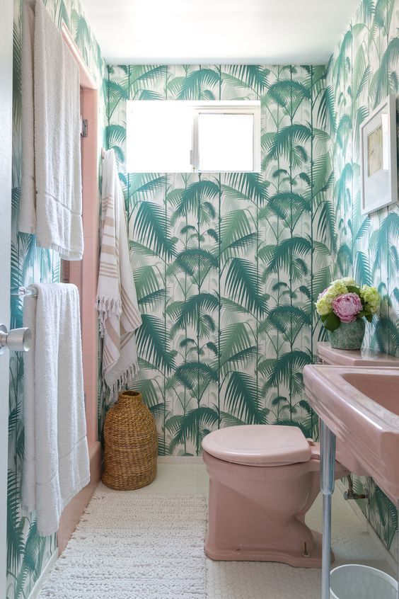 a bright tropical bathroom with tropical wallpaper, a pink sink and toilet, neutral linens