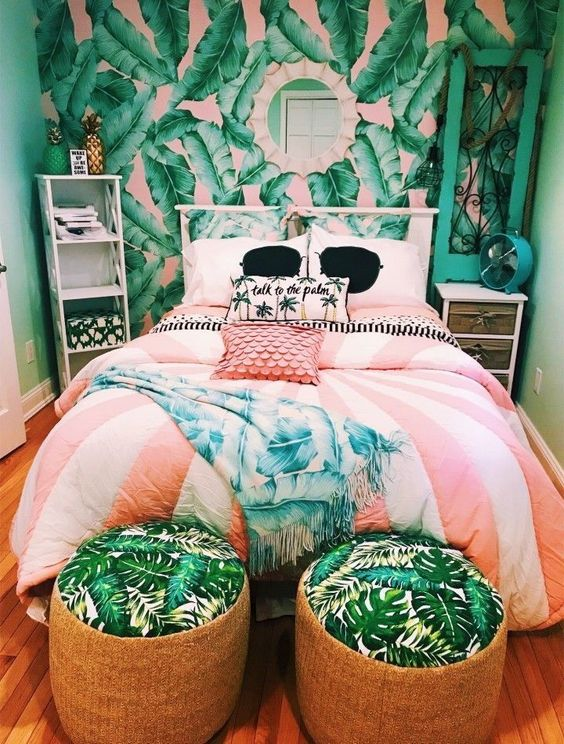 a bright tropical bedroom in green and pink, with wicker ottomans, bright bedding, a pink and green tropical print statement wall