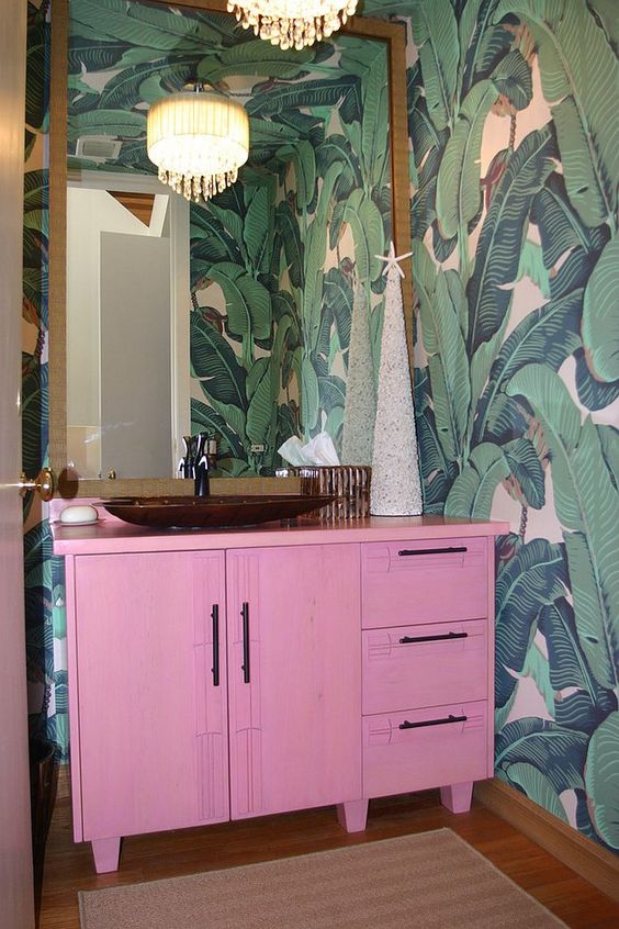 a bright tropical powder room with banan leaf wallpaper, a hot pink vanity, a statement mirror and a vintage chandelier