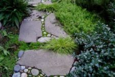 a catchy and bold stone garden path with moss, smaller rocks in betwee and some grasses growing