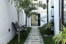 a catchy and natural garden path of grey large scale pebbles and stone tiles on top