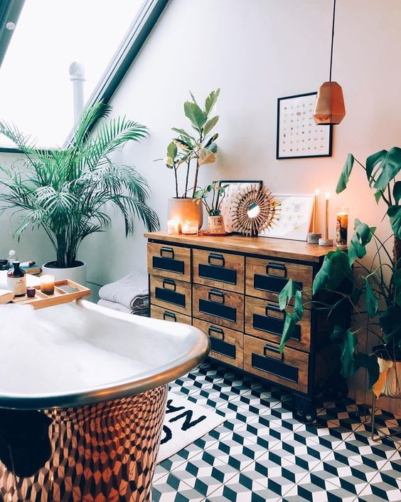 a catchy attic tropical bathroom with a vintage storage unit, a copper clawfoot tub, potted plants and candles plus copper touches