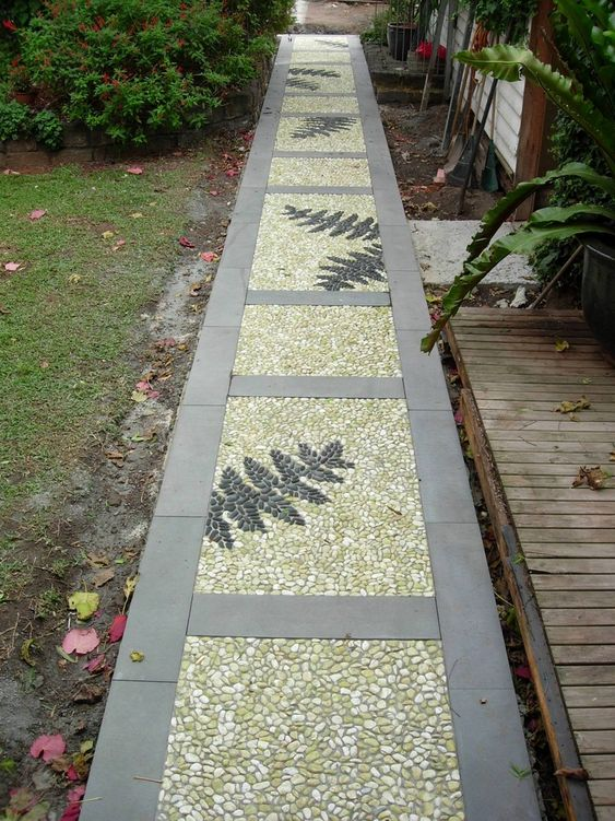 a catchy pebble garden path with neutral stone tiles, neutral pebbles and fern leaves done with black pebbles