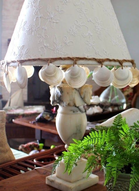 a catchy seaside table lamp of stone, with seashells hanging on the lampshade is a cool and bold idea