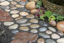 a catchy stone garden path with round muted color stones and leaf-shaped stones