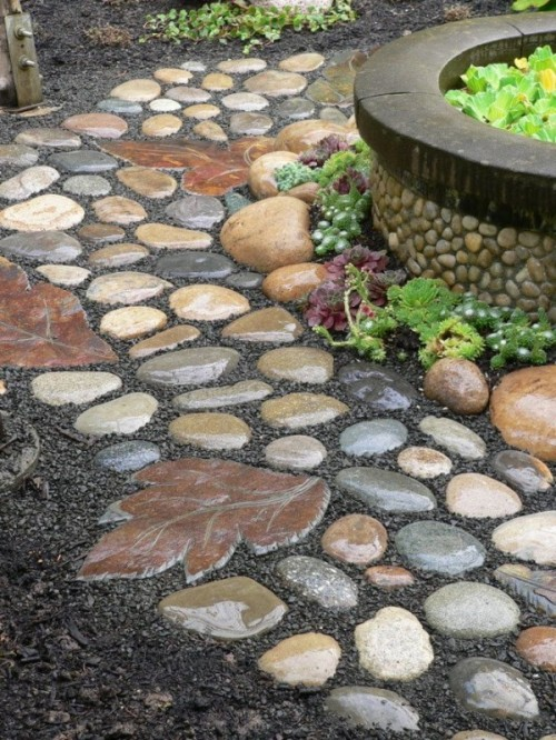 a catchy stone garden path with round muted color stones and leaf shaped stones