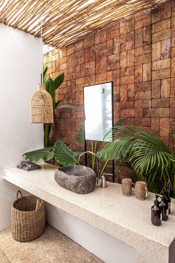 a catchy tropical bathroom with a brick wall, a stone vanity, a stone sink, a woven lamp and a basket