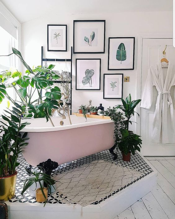 a catchy tropical bathroom with a pink clawfoot tub on a platform, a tropical gallery wall, potted plants and mosaic tiles