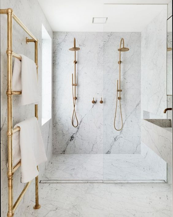 a chic and elegant bathroom done in white marble and gold hardware plus a floating sink and vanity