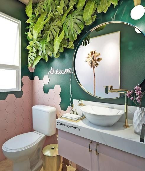 a chic and fun tropical bathroom with emerald walls, pink hex tiles and a pink vanity, a tropical leaf decoration and gold touches