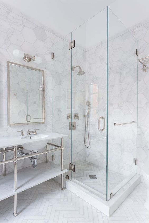 a chic bathroom with white marble hex tiles and a herringbone pattern on the floor plus neutral hardware
