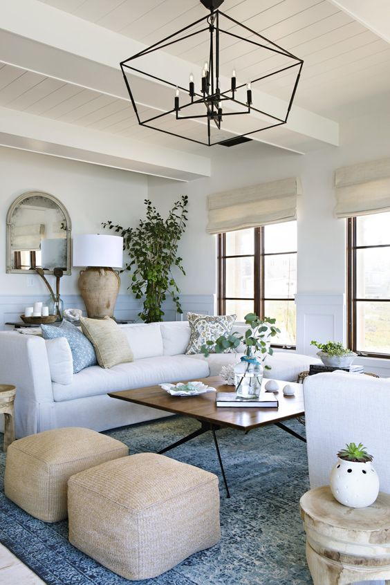 a chic coastal living room with touches of blue and light blue, creamy furniture and tan items plus a dirftwood lamp