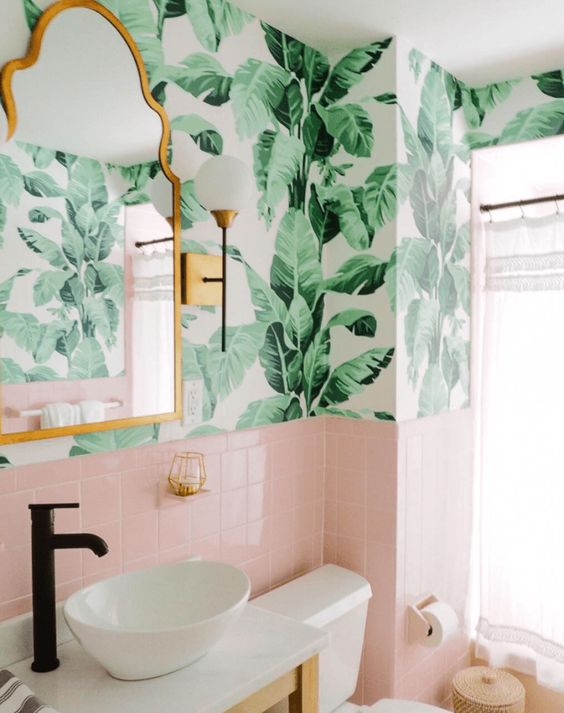 a chic tropical bathroom wiht tropical wallpaper, pink tiles, a bowl sink and touches of brass