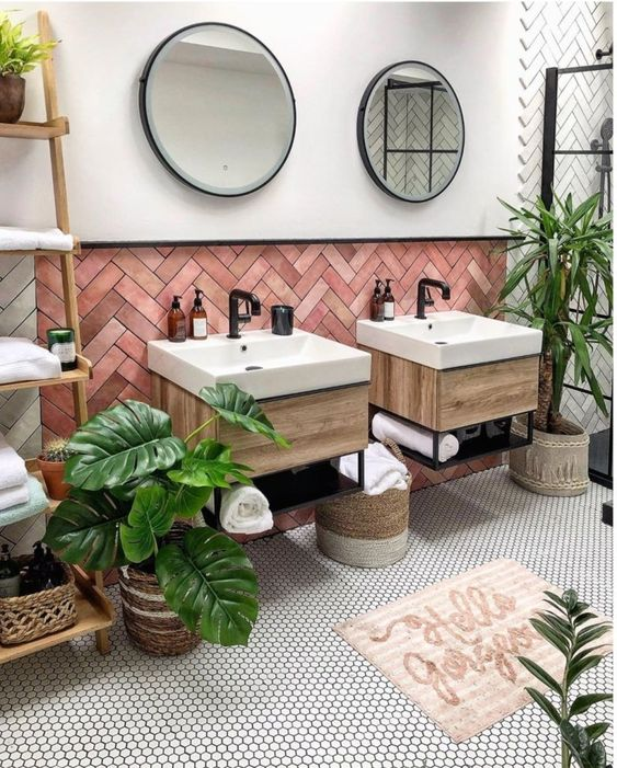 a chic tropical bathroom with pink herringbone clad tiles, floating vanities, potted plants, penny tiles and baskets