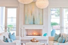 a chic white beach living room with aqua and turquoise touches, fluffy pendant lamps, a fireplace