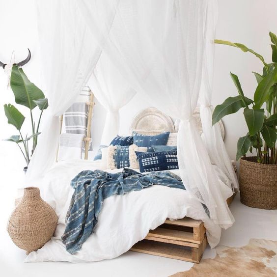 a clean and airy tropical bedroom with a pallet bed with an airy white canopy, wicker pots with green leaves or plants