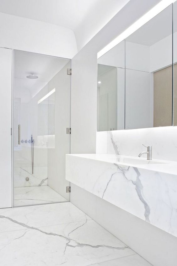 a clean minimalist space done with whte marble, a mirror with lights, a shower space and a marble vanity