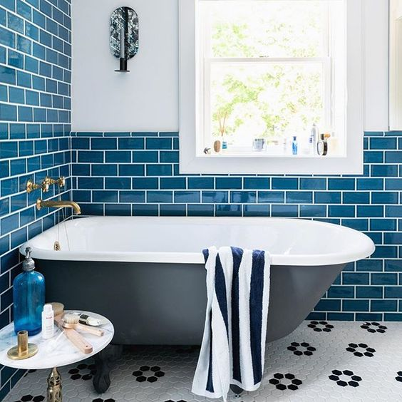 a coastal-inspired bathroom with navy subway tiles, a black bathtub and some cute accessories