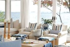 a coastal living room with gorgeous views, stripes, blues and much wood in decor