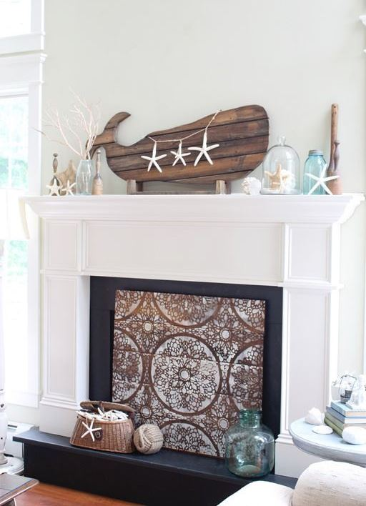 a coastal mantel with a wooden whale with starfish, starfish, bottles and jars with corals and seashells