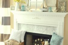 a coastal mantel with corals, starfish, seashells, a candle lantern, blue jars and blooming branches in a jug