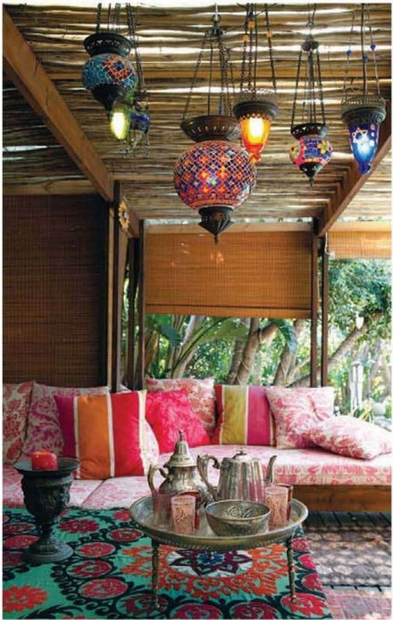 a colorful Moroccan patio with lots of bright mosaic lanterns, a printed pink sofa, a low coffee table with coffeeware