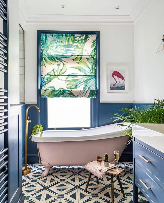 a colorful bathroom with a tropical feel, blue paneling and furniture, mosaic tiles, a pink tub, a tropical curtain and potted plants
