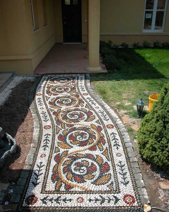 a colorful mosaic pebble garden path with yellow, red and green pebbles will accent your garden a lot