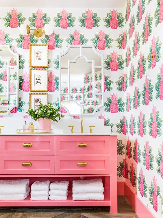 a colorful tropical bathroom with pink pineapple wallpaper, a hot pink vanity and potted greenery and gold touches
