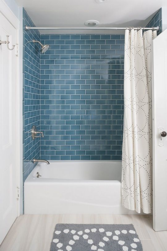 a comfy modern bathroom with blue subway tiles, a white tub and all neutrals around