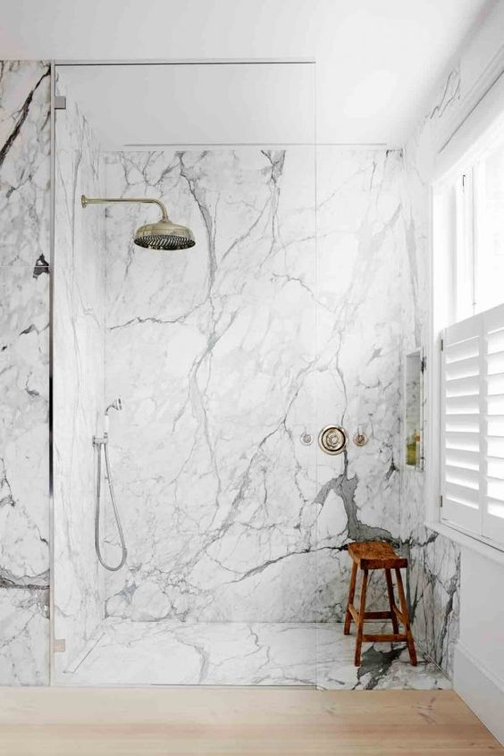 a contemporary bathroom with white marble, sleek wood and vintage hardware for a bright and chic look