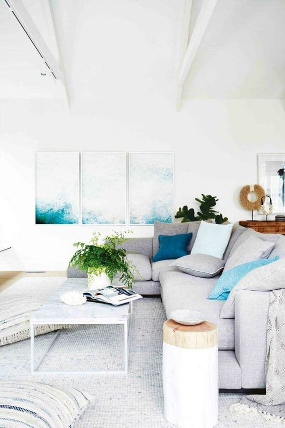 a contemporary coastal living room with bold artworks, neutral furniture, a tree stump side table and a rug