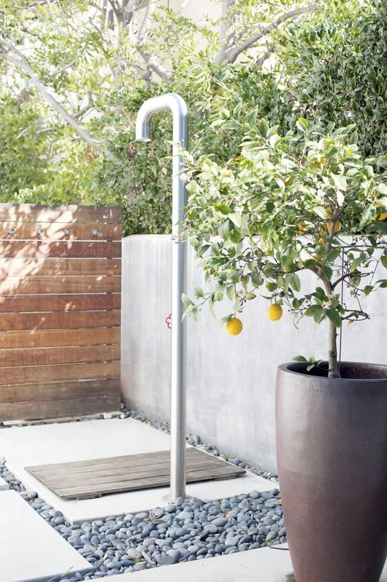 a contemporary outdoor shower done with pebbles, concrete and wood and potted lemons for an ambience